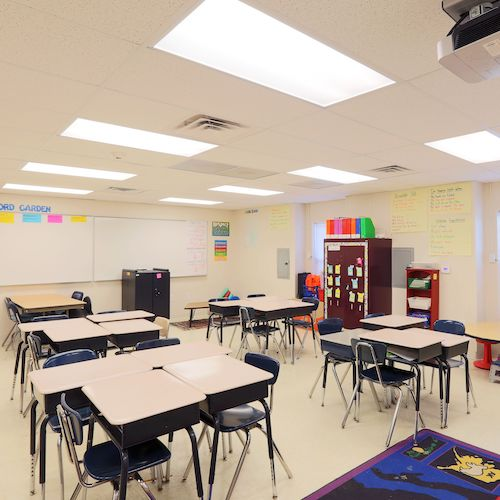 Empty classroom furnished with desks, chairs and dry erase board