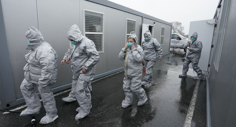 People in protective suits outside mobile office trailers