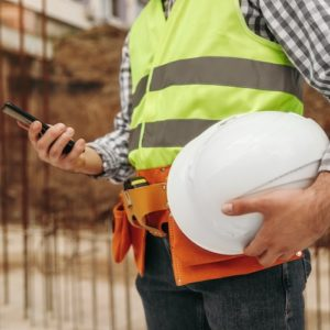 Construction worker on his phone holding a hat